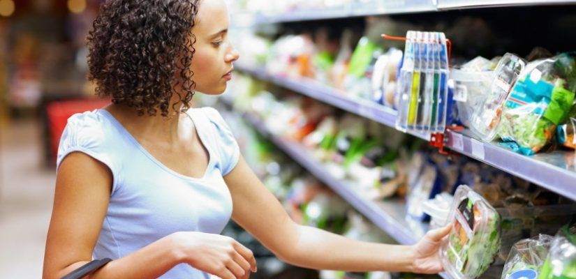 Attractive mixed race woman reading label of food item at supermarket
